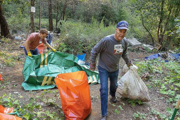 Nevada County Supervisor Dan Miller, right, and Grass Valley City Manager Tim Kiser move garbage out of the camp, in bags provided by Waste Management.