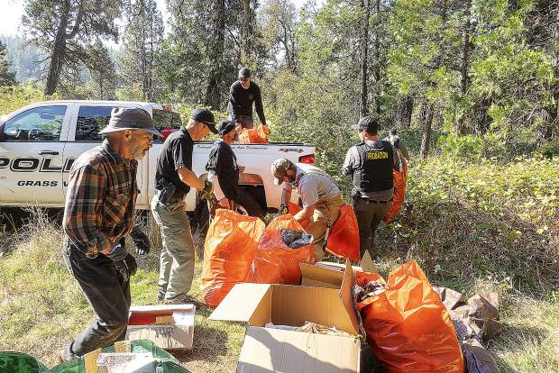Volunteers pile up trash bags in Grass Valley Police pickup truck.