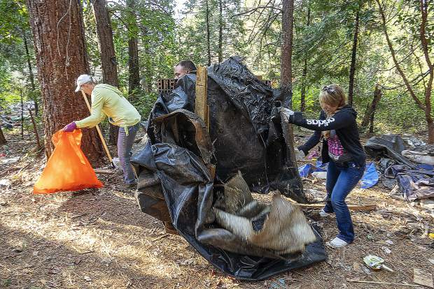 Volunteers move trash out of an abandoned homeless camp.