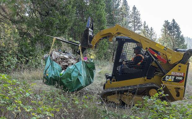 Heavy equipment helps haul a large bag up the hill to a loading zone during a clean-up effort of a homeless camp on private land in Grass Valley's Glenbrook Basin Saturday. Hospitality House joined with the County of Nevada, City of Grass Valley, Nevada County Sheriff's Office, and Grass Valley Police Department to clean up a camp near near Plaza Drive..