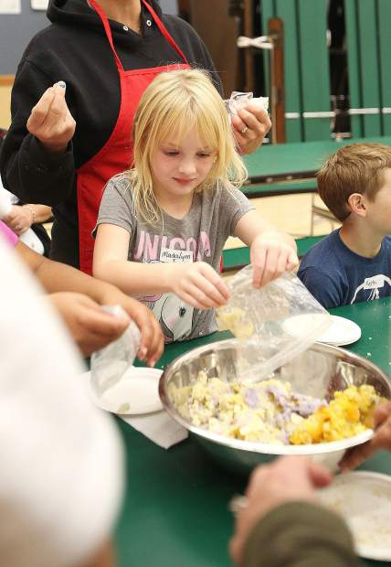 Chicago Park Elementary's Madalynn Funk places her mashed potatoes into a bowl to be mixed before making them into tater tots.