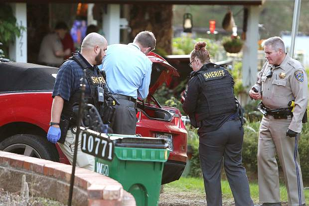 Law enforcement detectives and officers inspect the trunk of the red Camaro that led them on a brief chase before a collision occurred in the 10000 block of Pittsburg Road Wednesday evening.