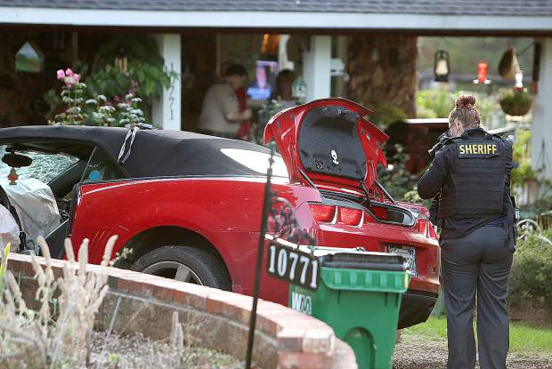 Crime scene officers photograph the contents in the truck of the red Camaro while others question the residents of the home in the 10000 block of Pittsburg Road Wednesday evening.