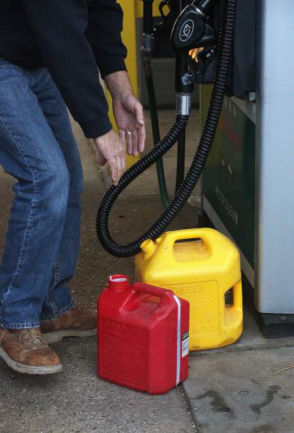 Folks fill up their extra gas cans and tanks Wednesday morning at Robinson Gas Station off of Lower Grass Valley Road.
