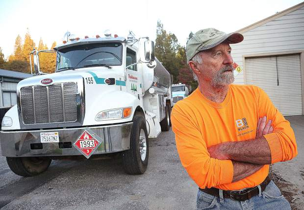 Robinson Enterprises tanker driver Bob Noller looks on while a line forms for pumps at the Robinson fleet fueling station on Lower Grass Valley Road in Nevada City where the only gas station in the area was working during a PG&E power shutoff. The shutoffs caused students to miss a lot of instruction time this fall.