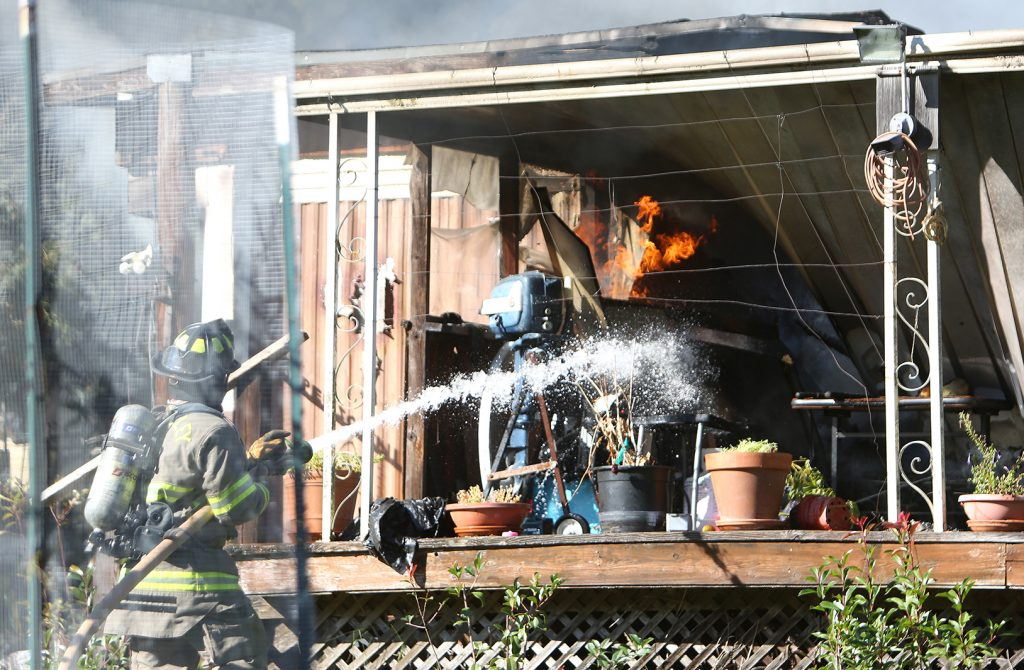 Firefighters get water onto a single wide mobile home off of Personeni Lane in Rough and Ready that was completely destroyed in an early morning structure fire.