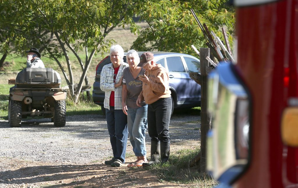 Neighbors console one another as they watch a home burn on the 13,000 block of Personeni Lane in Rough and Ready Thursday morning.