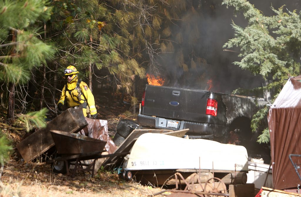Firefighters check the surrounding wildland for extension behind the Personeni structure fire Thursday morning.