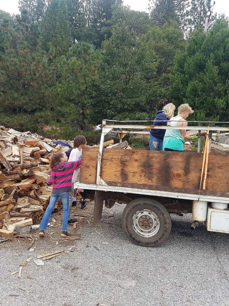 Volunteers for the Senior Firewood Program load up firewood to help seniors stay warm this winter.