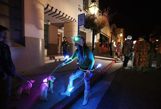 Nevada City's Darby Palmer, with her dog Prince, was one of about 30 people who participated in an impromptu light parade/protest that took place following a Nevada City council meeting.