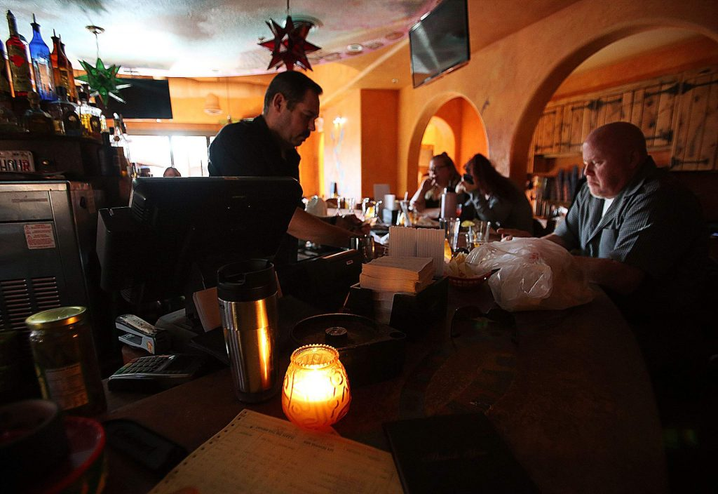 Maria's restaurant staff work in candlelight as they choose to stay open with a limited menu offering Wednesday evening after losing power in downtown Grass Valley.