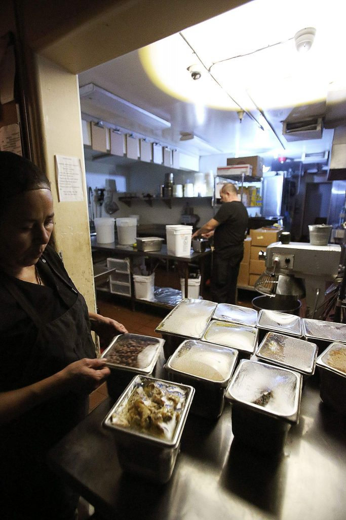 Maria's restaurant employees work by battery powered lamps in the kitchen following the power shutdown in Grass Valley Wednesday.