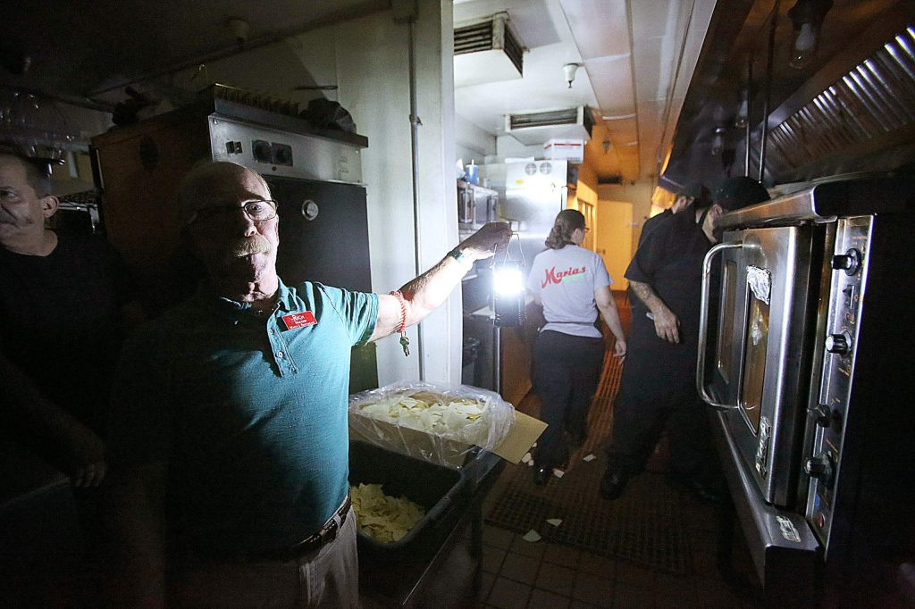 Maria's restaurant manager Rich Fuxjager holds a battery powered lamp in the kitchen of Maria's restaurant as they continue to work with a limited menu following Wednesday's power outage.