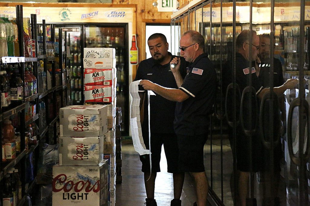 Workers at Penn Valley Market & B Liquor check their beer order with the help of generators and flash lights during the power shutdown Thursday morning.
