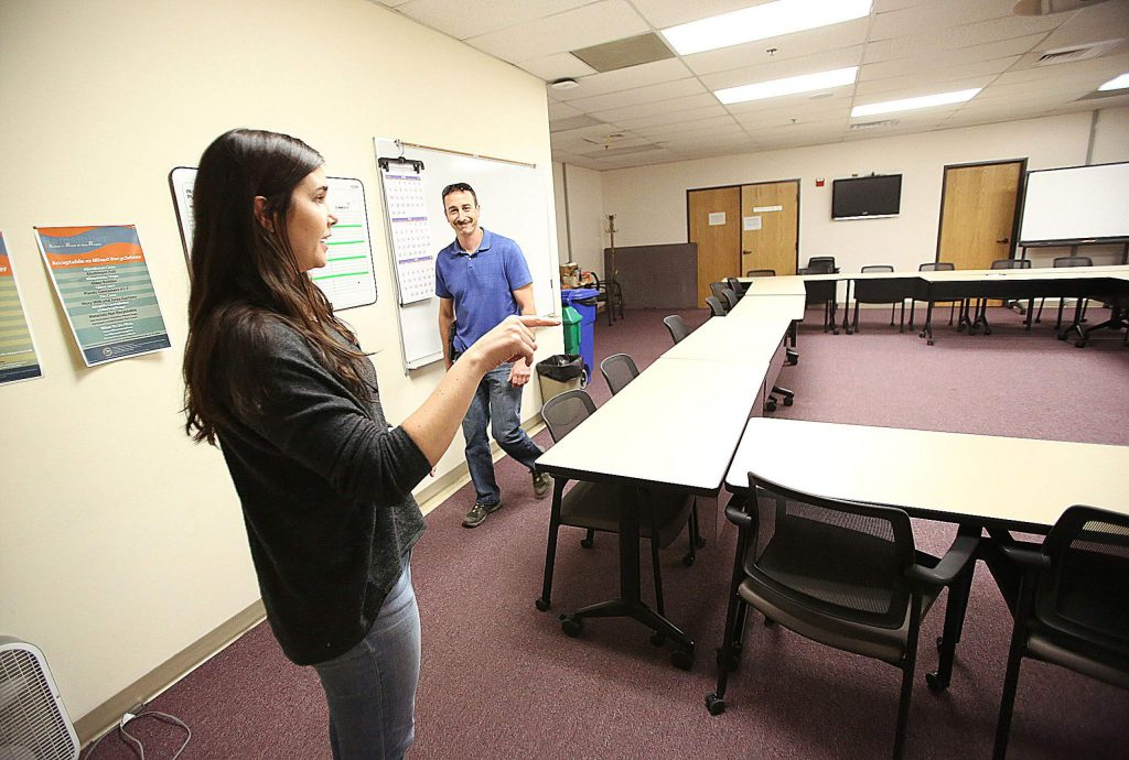 Taylor Wolfe stands in an overflow planning room that can be staffed with 211 connecting point staff when their offices lose power so that they can continue to man the phones and relay important information.