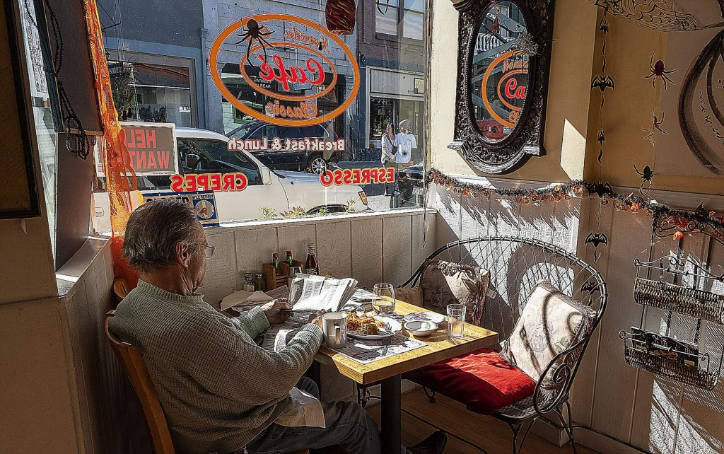 Lee Daugherty read the paper and ate lunch using the sunlight through a window of Nevada City's Classic Cafe on Broad Street Tuesday afternoon. PG&E's Public Safety Power Shutoff affected Nevada City, surrounding areas and several counties in Northern California on Tuesday.