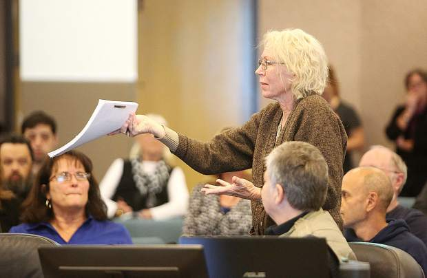 Jan Weaver holds up a copy of the Emergency Access Roads Report completed in the year 2000 during Thursday evening's joint town hall meeting hosted by District 1 Supervisor Heidi Hall and NID Division 1 Director Ricki Heck. Weaver wanted an update on the report.