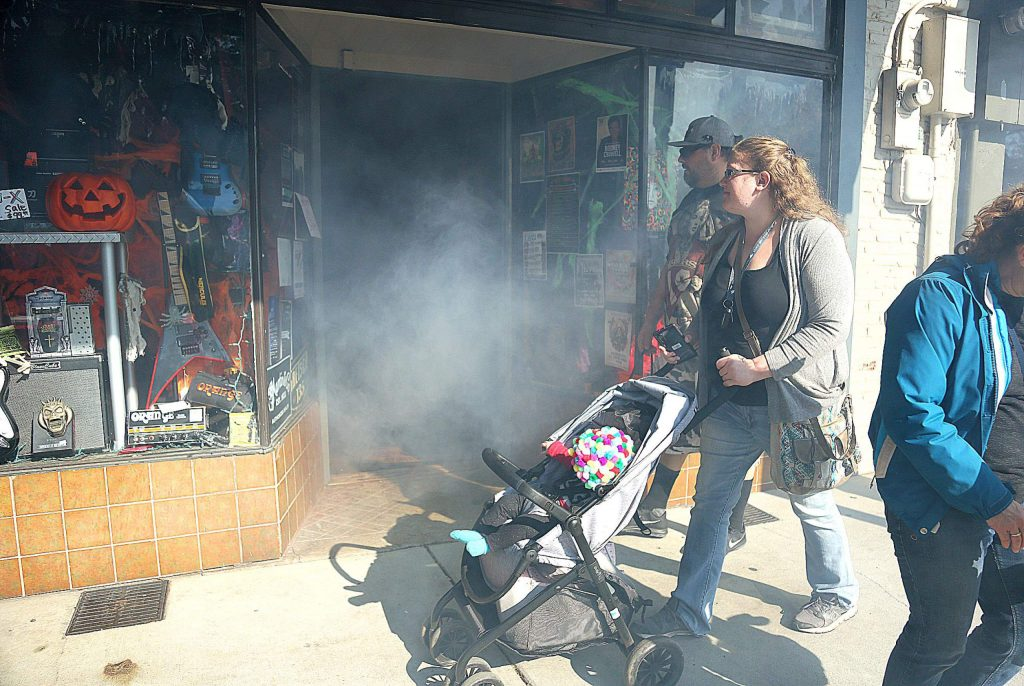 Fog permeates out of Foggy Mountain Music while the shop keepers hand out candy to children inside.
