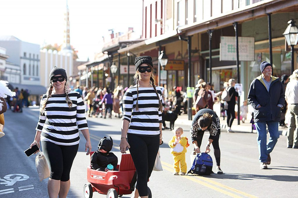 Leah Bell and Stephanie Kish, dressed as burglars, pull Axel Bell dressed as Batman.