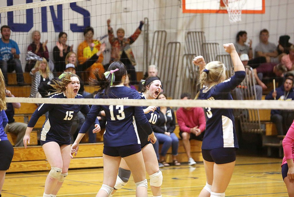 The Forest Lake Christian Falcons varsity girls volleyball team celebrates after scoring a point over their first round playoff rivals Thursday evening at home.