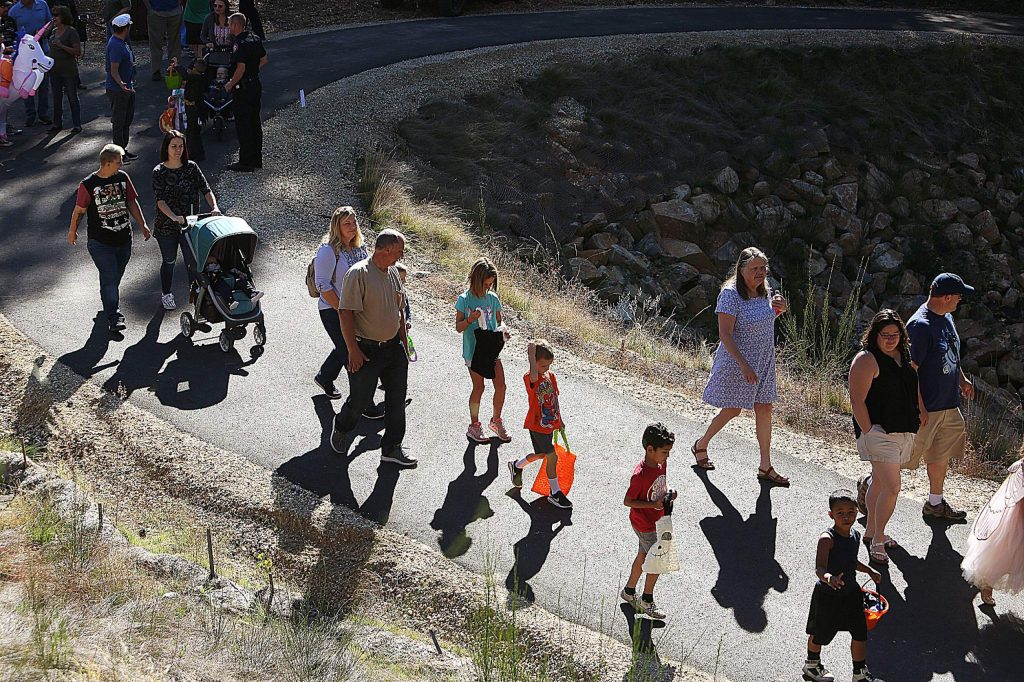Young trick-or-treaters and their families begin their walk along the Wolf Creek Trail from the Little Wolf Creek sinkhole access.