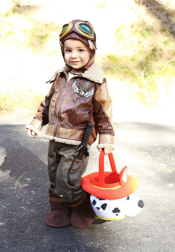 Amalia Gat smiles as she trick-or-treats as Amelia Earhart Saturday morning along the Wolf Creek Trail.