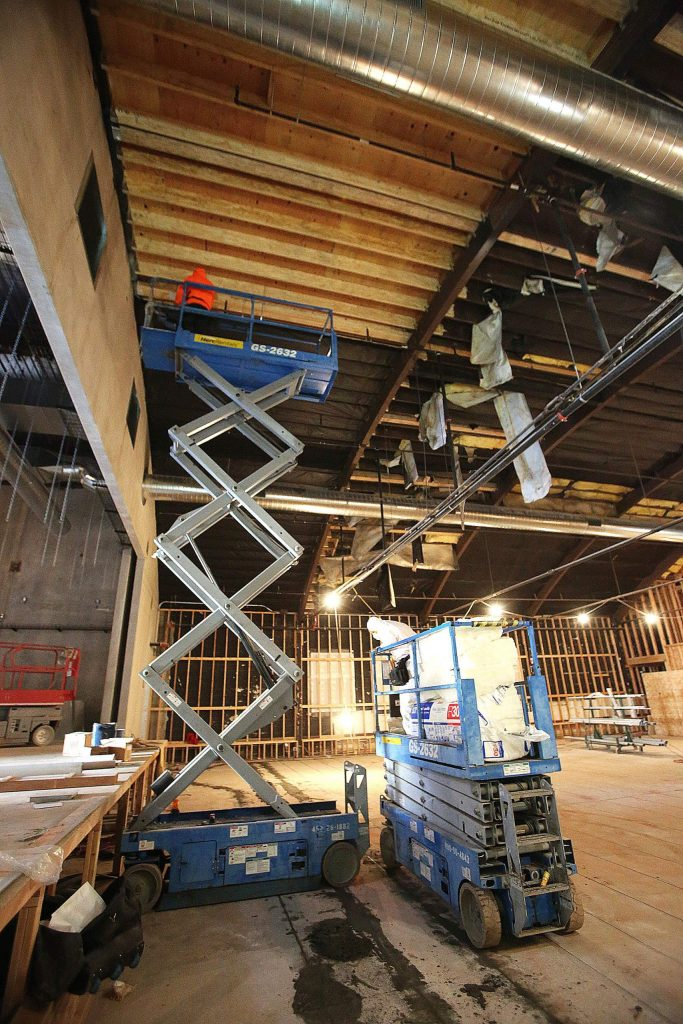 Inusulation installers work atop a scissor lift in front of the proscenium of the Center for the Arts stage.