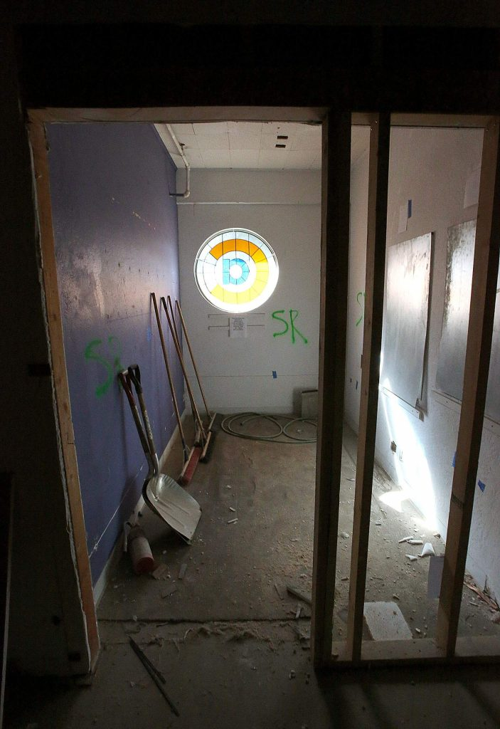 Construction material sits in a rooom illuminated by a Center for the Arts stained glass window during remodeling construction this week.