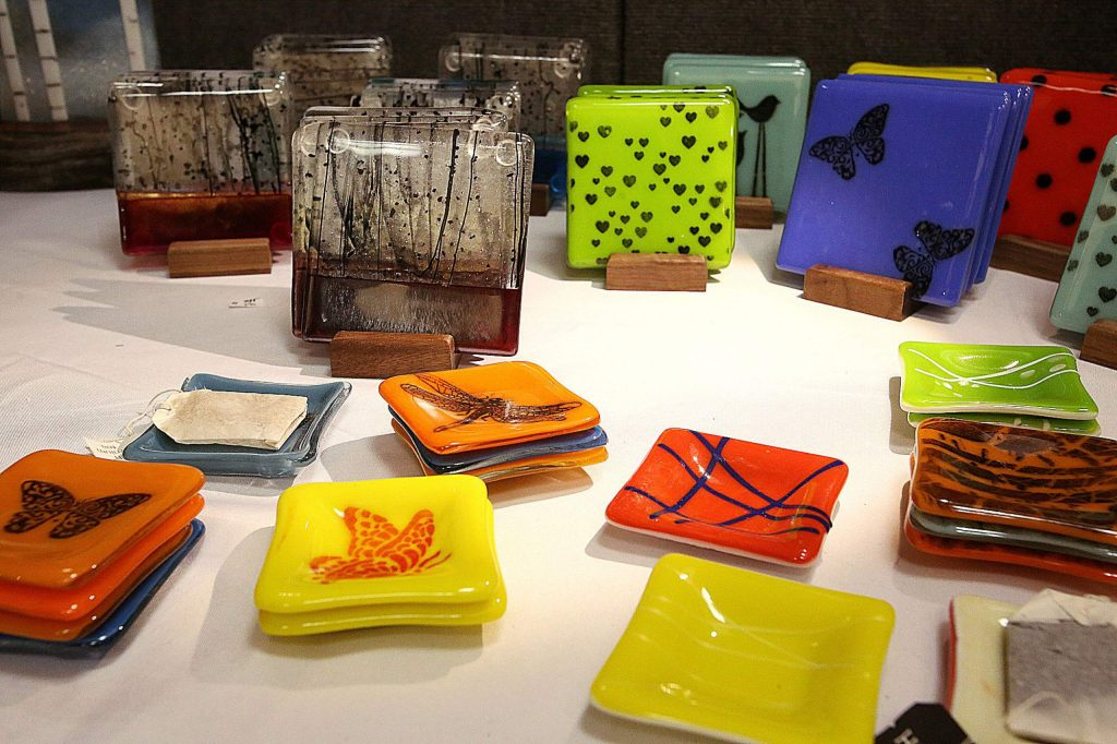 Jan Anderson's Designs by Jan include colorfully and artistically designed coasters and tea bag holders.