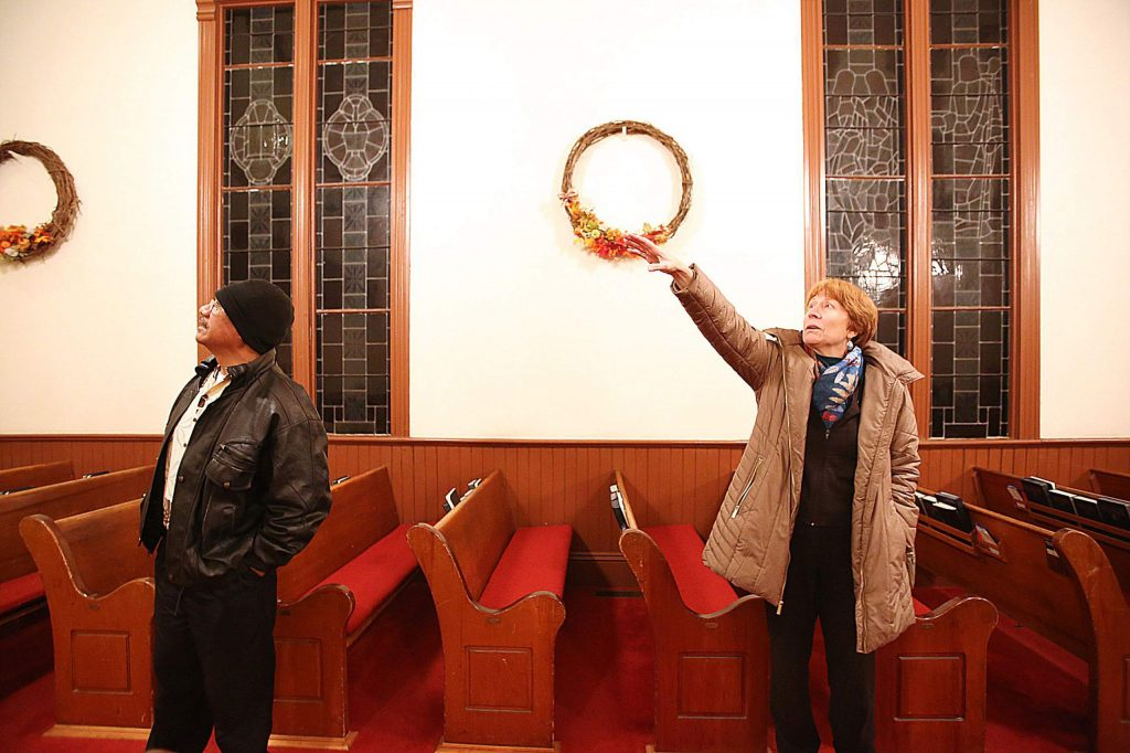 Nevada City United Methodist Church's Mary DeWitt stands with current pastor David Niu, and talks about some of the things that the movie crew did while filming the church's scenes in The Christmas Card.