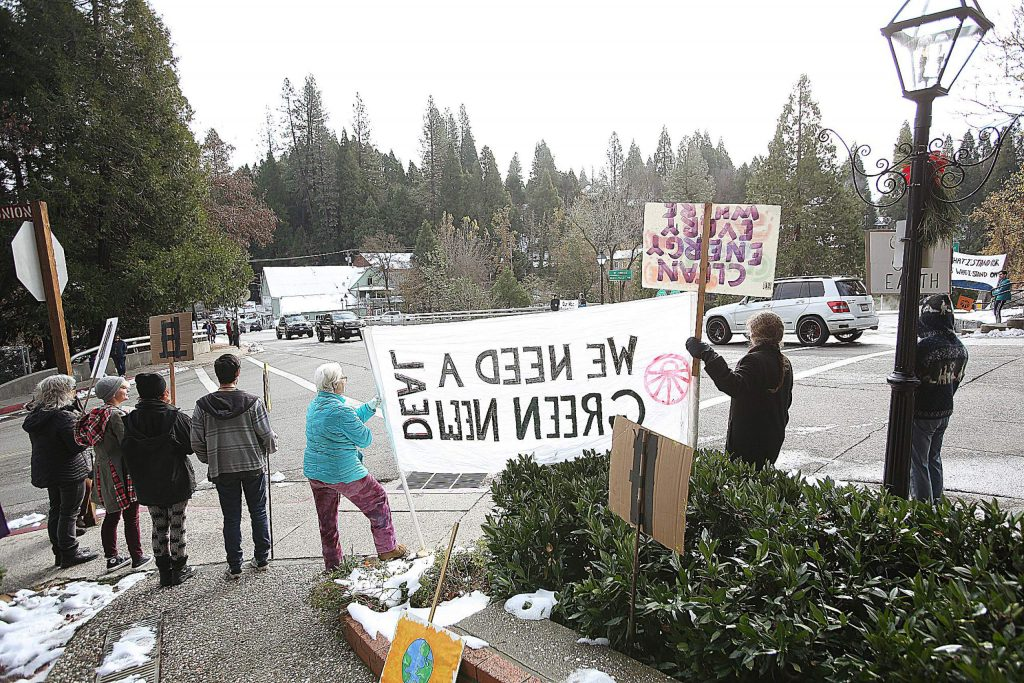 Nevada County Sunrise Movement activists hold signs promoting climate change awareness and green energy.