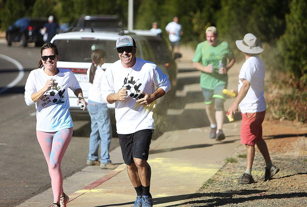 A pair of runners smile as they take part in the Nevada Union girls soccer Kick Run Color 5k now in its second year.
