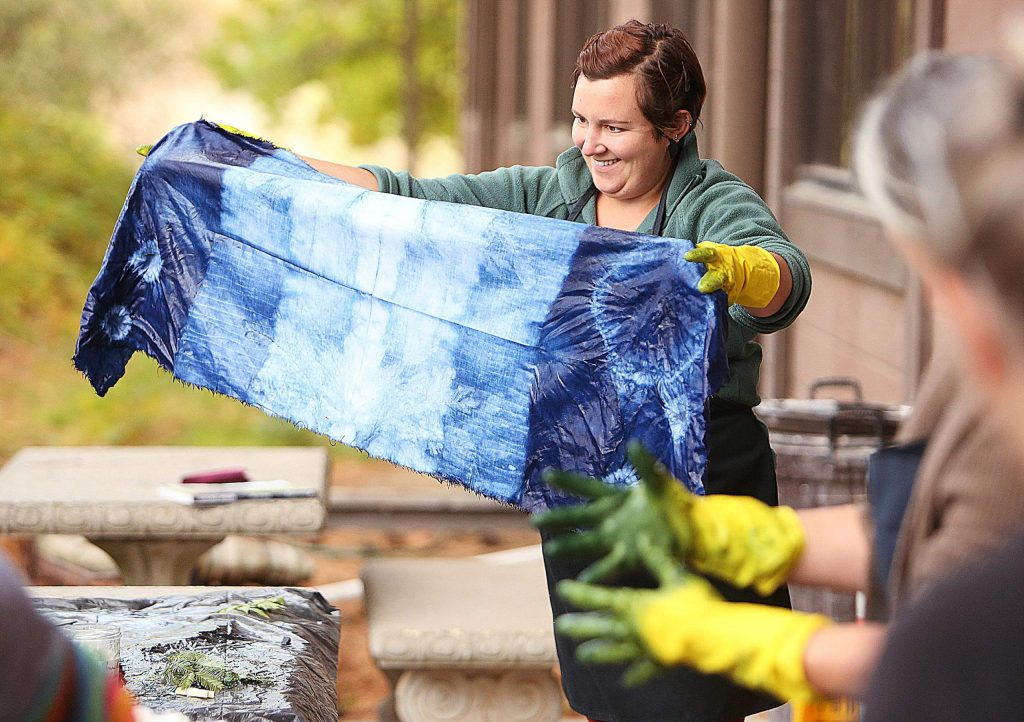 Emily Baxter unties her indigo dye creation and is quite pleased with the results.