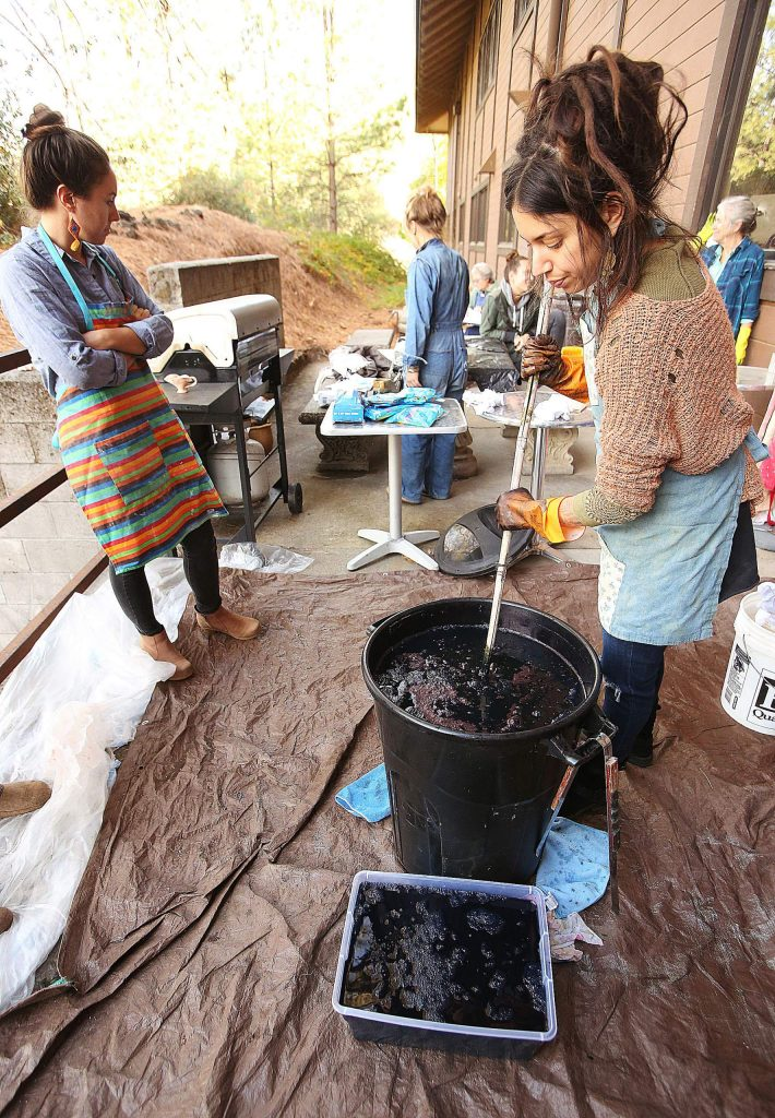 Curious Forge Shibori indigo dye class instructor Eileen Holzer adds a mixture of indigo dye, soda ash and sugar to the tub to allow for participants to get that deep indigo color in their creations during Saturdays workshop.