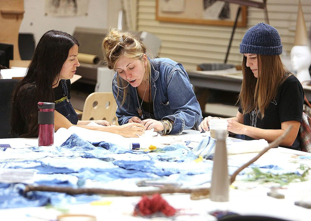 Co-instructor of Saturday's indigo dye workshop, Audra Ogden, helps class participants with their wrapping and tying techniques that will be used to make specific patterns on their linens once added to the vat of indigo dye.