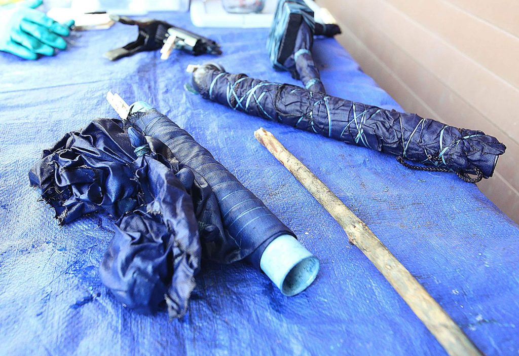 A collection of indigo dyed creations sit wrapped and tied up for an hour before they can be unraveled and dried.