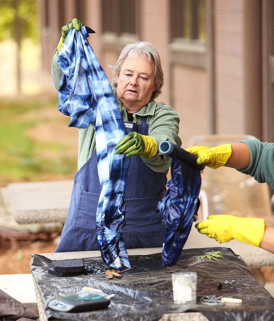 Sandy Feyh begins to untie her indigo dyed creation Saturday afternoon during the class that focused on the Japanese Shibori style indigo dye process.