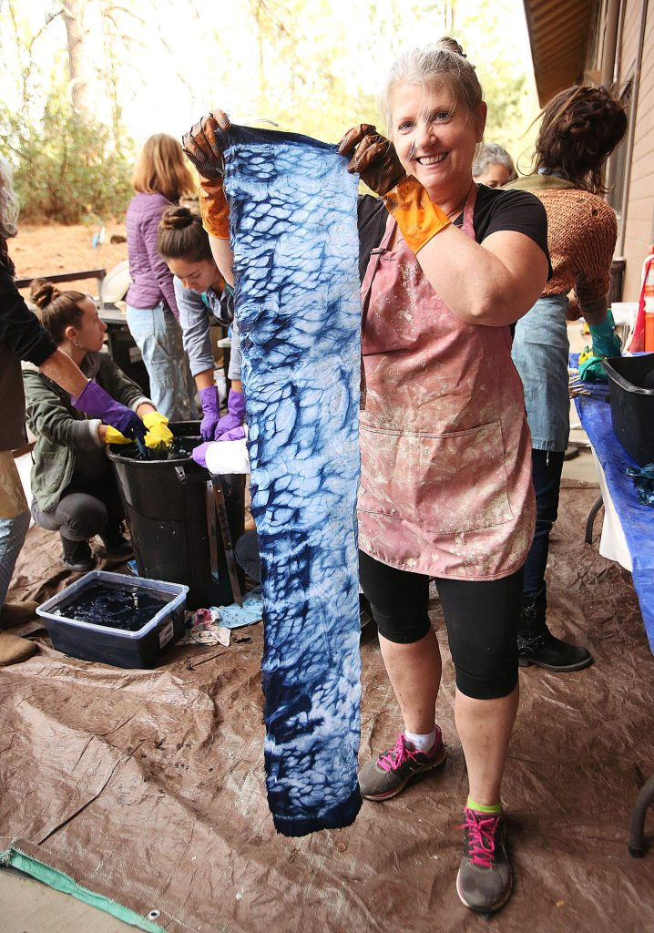 Betsy Swannbrown holds up one of her indigo dyed linens created Saturday at the Curious Forge during one of their many workshops offered to members of the public and members of the maker space.