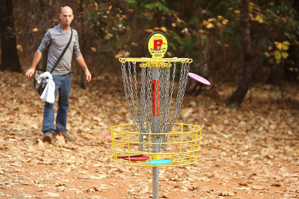 Penn Valley's Jeremiah Rogers watches as a putt nears the basket at the Squirrel Creek at Condon Park Disc Golf Course Wednesday. The park is set to receive $10,000 in upgrades. The park will add nine new holes, bringing the course to 27 holes total and will use the fairways as fire breaks.