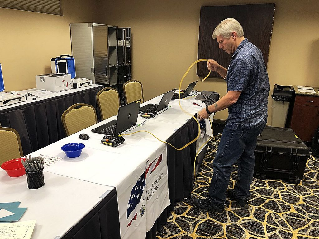 Mike Parker with county information systems sets up the voting system at the Gold Miners Inn.