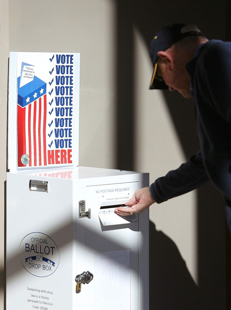 A ballot is dropped into one of the boxes in the downstairs lobby of the Eric Rood Administrative Center during election day Tuesday.