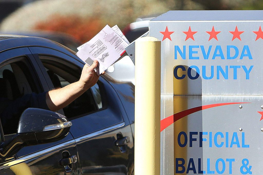 A handful of ballots is dropped into the drop box in the parking lot of the Eric Rood Administrative Center during Tuesday's election.
