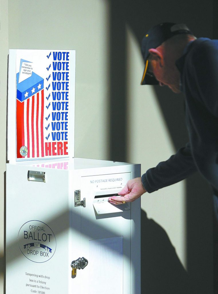 A ballot is dropped into one of the boxes in the downstairs lobby of the Rood Government Center during election day Tuesday.