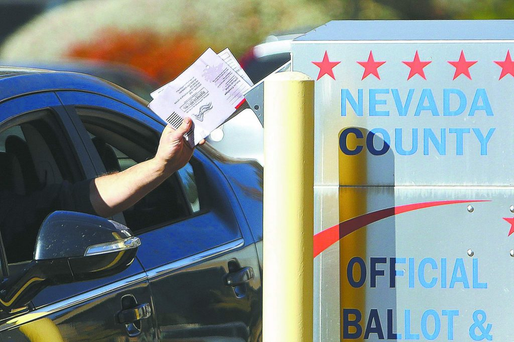 A handful of ballots are dropped into the drop box in the parking lot of the Rood Government Center during Tuesday's election.