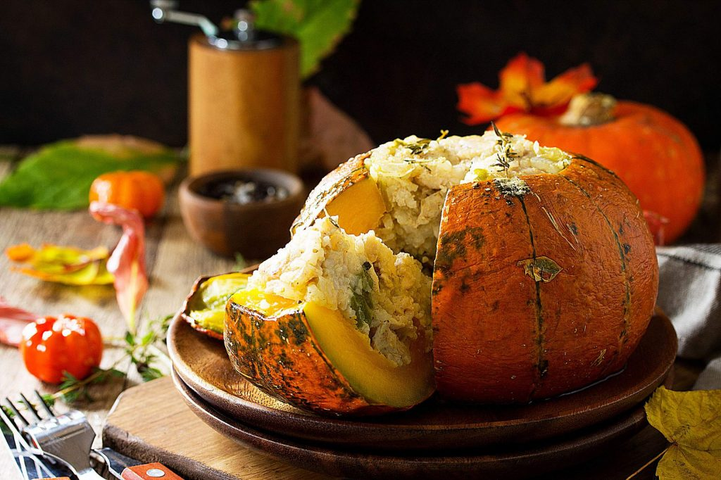 Thanksgiving Turkey dinner. Baked pumpkin stuffed with Turkey, rice and vegetables on rustic background. The concept of food on thanksgiving. Copy space.