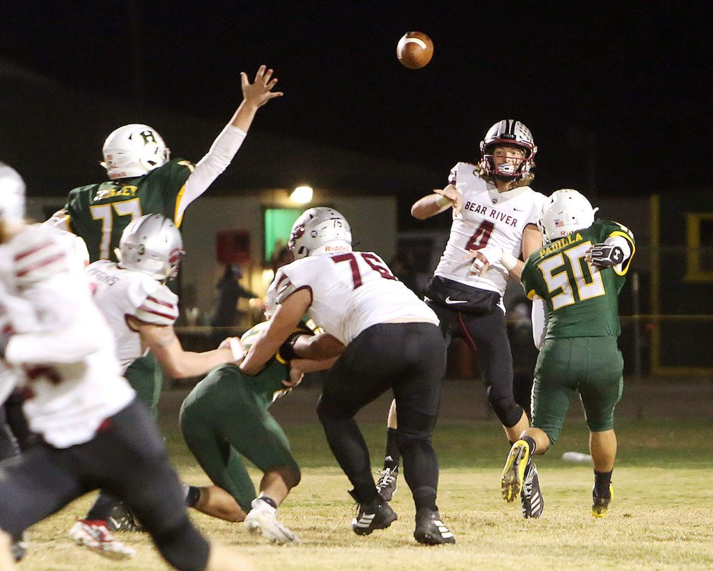 Bear River quarterback Tre Maronic (4) makes a pass for a completion while under pressure from the Yellowjackets defense Friday night in Hilmar.