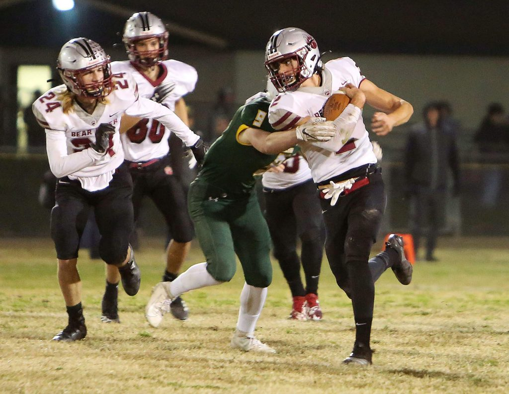 Bear River ball carrier Colton Jenkins (2) fends off a swarm of Yellowjackets during a kickoff return at Friday's second round Sac Joaquin Division VI playoff game against Hilmar.