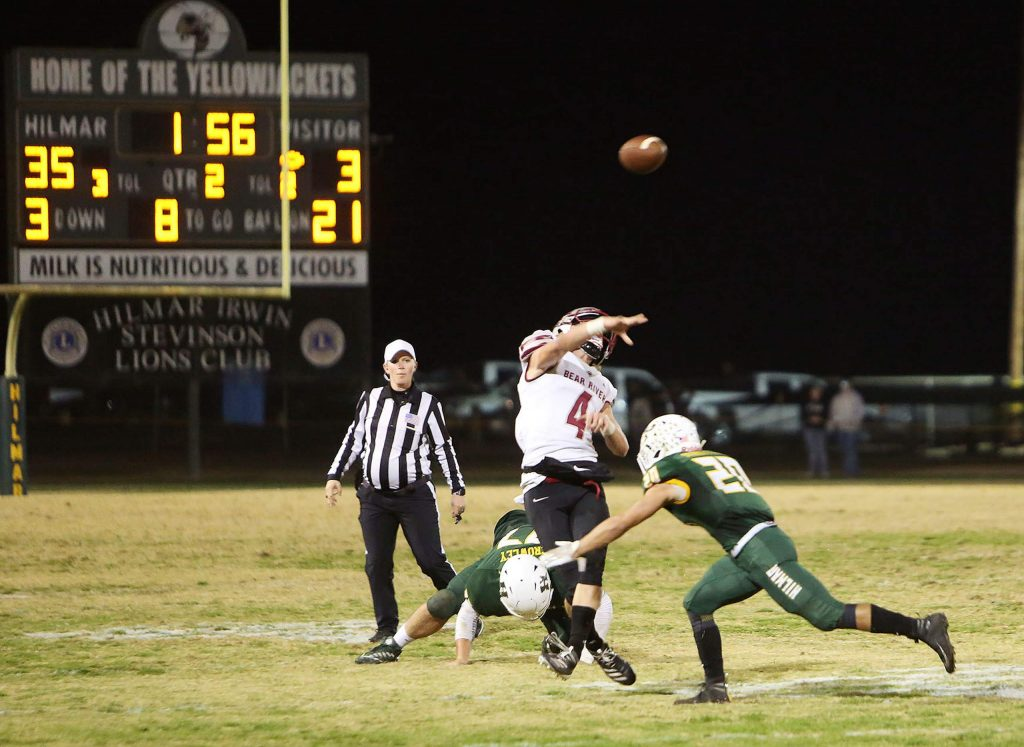 Bear River quarterback Tre Maronic (4) makes a deep pass for a completion while under pressure from the Yellowjackets defense Friday night in Hilmar. The Bruins were able to fight back in the second half but ended the game with a 49-17 loss.