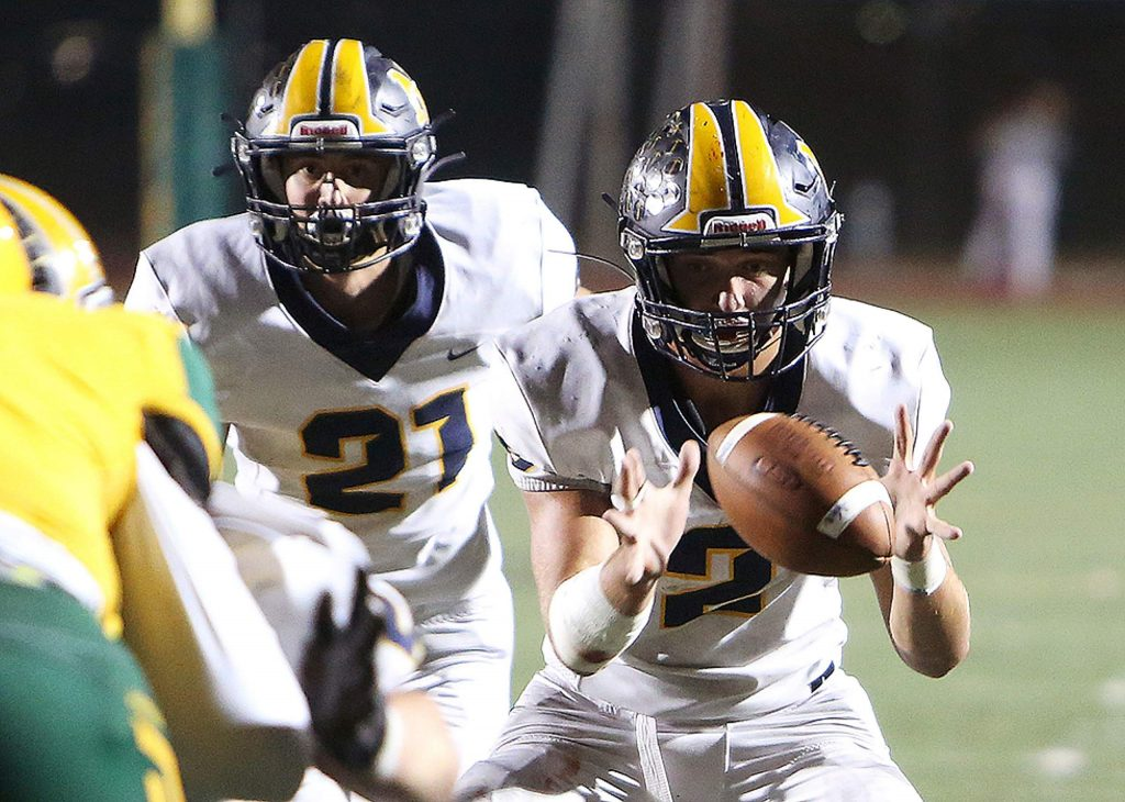Nevada Union starting quarterback Gabriel Baker (2) takes a snap before handing the ball off to team mate Jaxon Horne (21) during Friday's playoff loss to the Vanden Vikings.