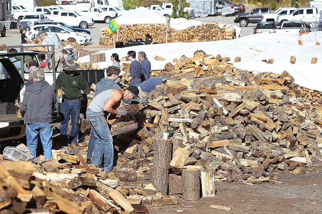 Mounds of split firewood await to be loaded into trucks and delivered to the 200 recipients of the senior firewood program. Logs come from community members as well as those who need help removing downed trees from their properties.